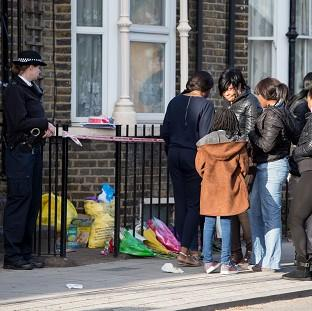 Herald Series: A police officer watches as a group of people gather at the scene in Hackney where Shereka Fab-Ann Marsh, 15, died after a shooting