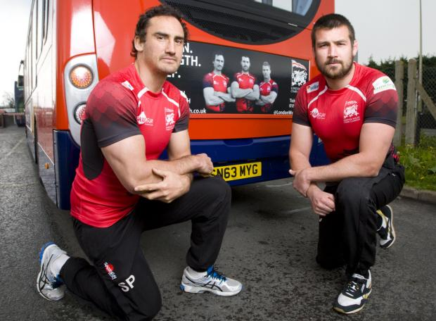 Herald Series: Sonny Parker (left) and club captain Matt Corker, who returns from a heart problem tomorrow, pose alongside their faces on the London Welsh's advert which also features Tom May and is appearing on Stagecoach buses in Oxfordshire