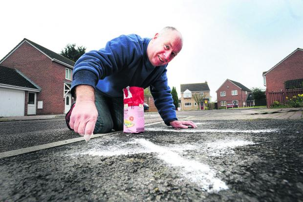Herald Series: Iain Belton draws some hash run markings outside his home in Bicester