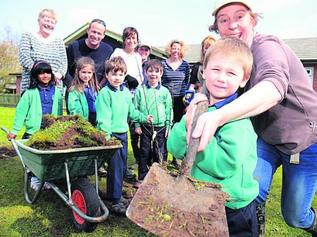 Callum Painter, five, and landscape architect Sue Chamberlin help pupils and parents plant trees as part of Fruitshare Project at St Laurence School in Warborough