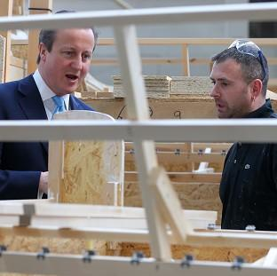 Herald Series: Prime Minister David Cameron talks to frame assembler Darren Jones during a visit to Westbridge Furniture Ltd, a sofa manufacturers in Greenfield, North Wales