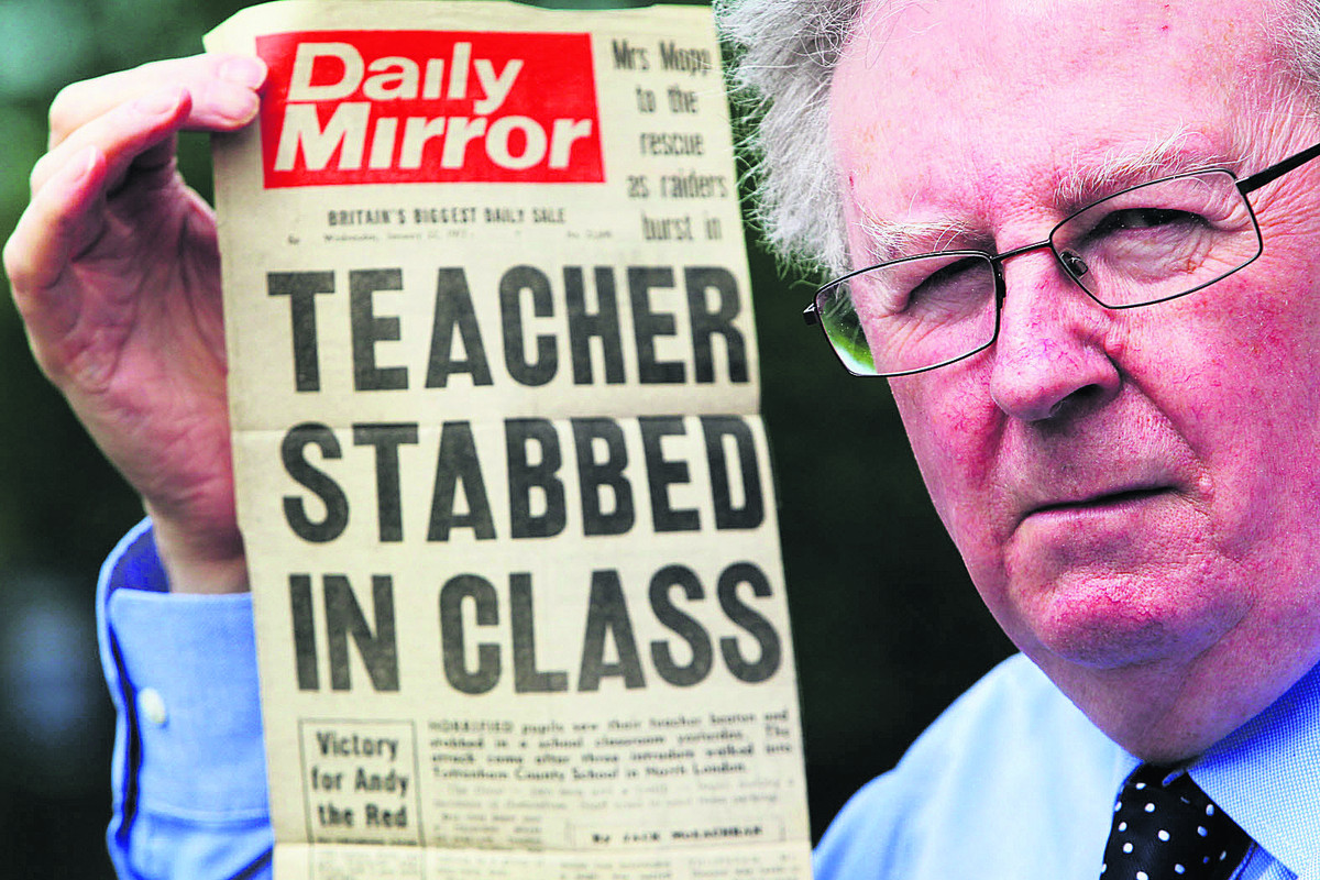 County councillor John Howson, above, with a copy of the Daily Mirror reporting on how he was stabbed in a London classroom in 1977