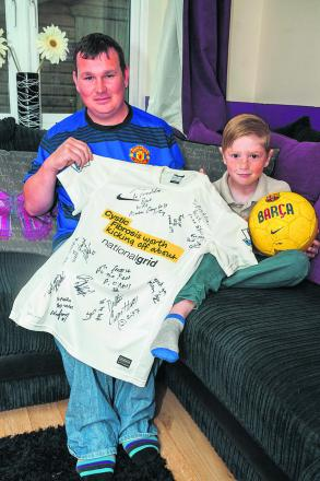 Fred Swanborough with his son Freddie, who suffers from cystic fibrosis, holding a shirt signed by celebrities ahead of the big match Picture: OX66688 Greg Blatchford