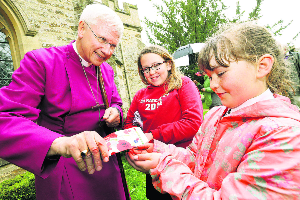 The Bishop of Dorchester, the Rt Rev Colin Fletcher, helps Dr Radcliffe's CofE Primary School pupils Charlotte Scrivens, 11, left, and Tilly Hancock, eight, plant poppy seeds at St Peter & St Paul Church, Steeple Aston.  Picture: OX66926 Damian Halliwel