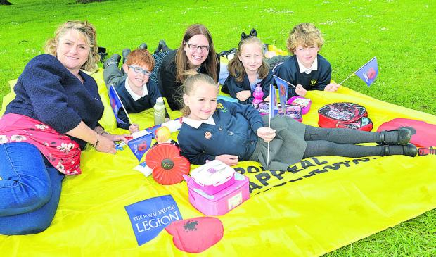 Laura Towell, left, Royal British Legion community fundraiser for Oxfordshire, and Bure Park School, Bicester, year five teacher Tina Woodgate with pupils, from left, Courtney Etheridge, seven, Dylan Morgan, seven, Lily Clare, six, and Brody Lloyd, five,