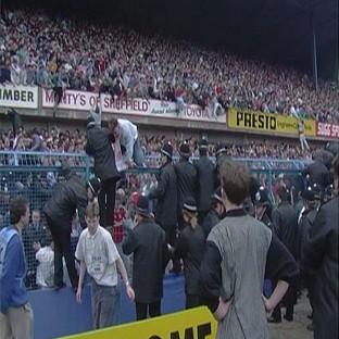 Herald Series: People climbing over the fence at the Leppings Lane end of Hillsborough Stadium as the tragedy unfolded