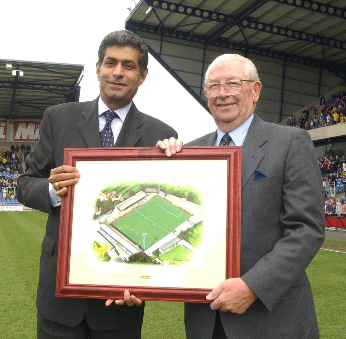 Firoz Kassam (left), Oxford United's chairman in 2002, presents Jack Casley with a painting of the old Manor Ground to mark his services to the club