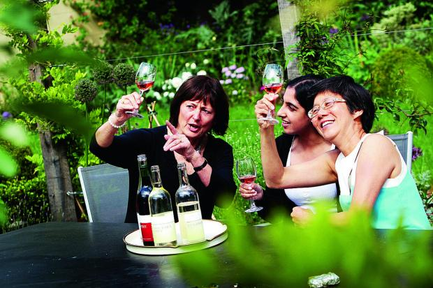 Herald Series: Reporter Annabal Bagdi, centre, is given advice on wine tasting ahead of the English Wine Festival, at Bothy Vineyard with, left, Denise Santilli from the Thames and Chilterns Vineyards Association and, right, Sian Liwicki