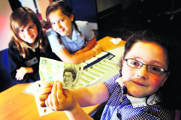 Cashiers, from left, Rhianna Thornton and Martha-Mae Preece, with Edie Attwood holding up her money.