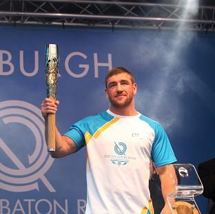 Alex Arthur carried the Glasgow 2014 Queen's Baton on to the stage as it ended the day in Edinburgh (David Cheskin for Glasgow 2014)