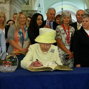 Herald Series: The Queen signs a book following her visit to the Belfast City Hall