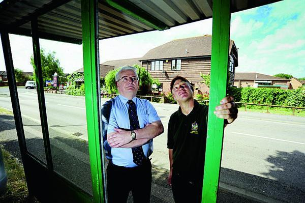 From left, Steve Rich, Head of Services and John Morris, from the Abingdon Town Council Works Team, inspects a bus shelter in Peachcroft Road that has had three of its windows smashed by vandals