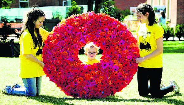From left, Catherine Sweeney, 14, Finley Stubbs, five, and Laura Burdess, 13, with the giant wreath
