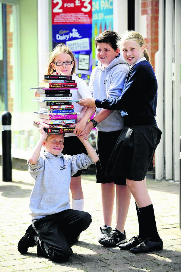 Eleven-year-olds, back from left, Erin Royan, Charlie Weeks and Hannah Spindler pile the books on Richard Bungay, also 11                      Picture: OX68473 David Fleming