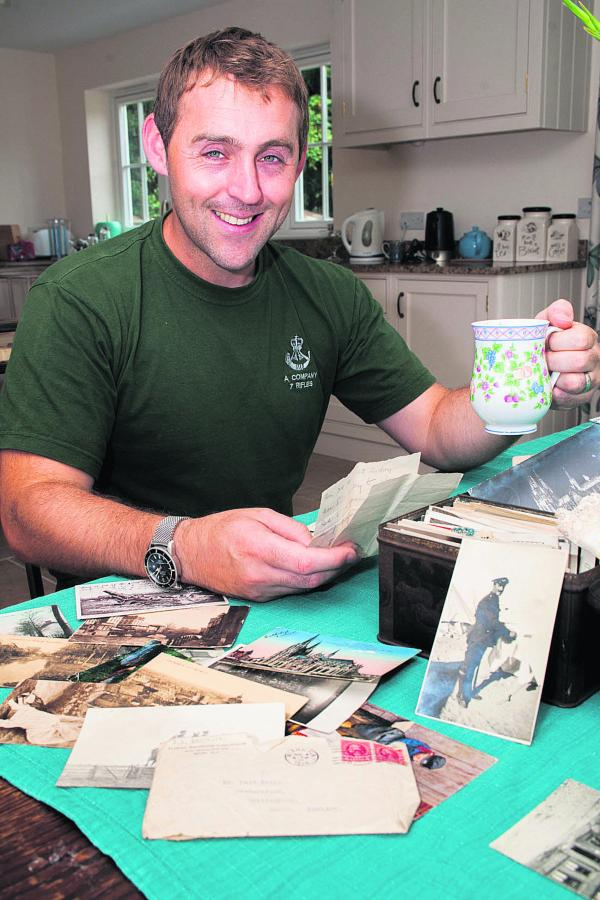 Adam Wheeler with postcards and other memorabilia about his great-grandfathers