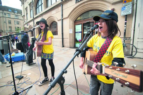 Nine-year-old Ace Manthey and his sister Sky, 12, busking in Carfax