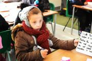 Pupil Tosia Swierkot sits through a lesson in her coat, scarf and hat