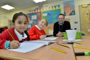 Cutteslowe Primary School pupils Samina Miah, seven, and Wiktoria Rodzik, eight, show off their writing skills with headteacher Jon Gray