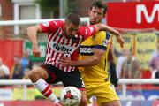 Liam Sercombe holds off Jake Wright while at Exeter last season