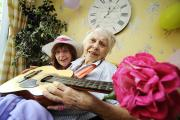 Flower power: From left, Wendy Pill, activities assistant, with Maria Roberts, 85, on the guitar