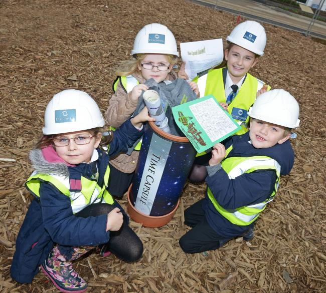 Past: From left, Izzy Wyatt, six, Bridget Fowles, six, Cerys Jeffrey and Harry Neale, six, with the time capsule