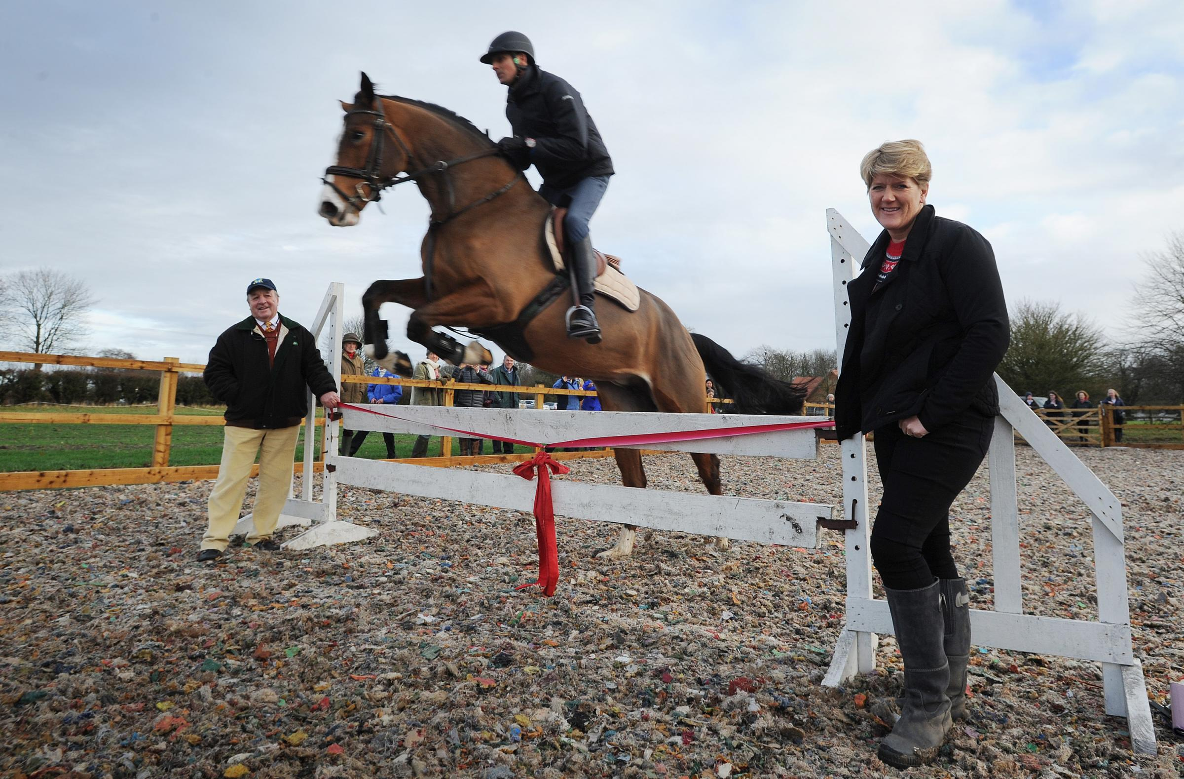 Clare Balding opening the new outdoor school at Letcombe Riding Club. She is pictured holding the ribbon with Richard Pitman as Fox, ridden by Nick Campbell, clears the fence. Picture: Jon Lewis.07.12.2017.
