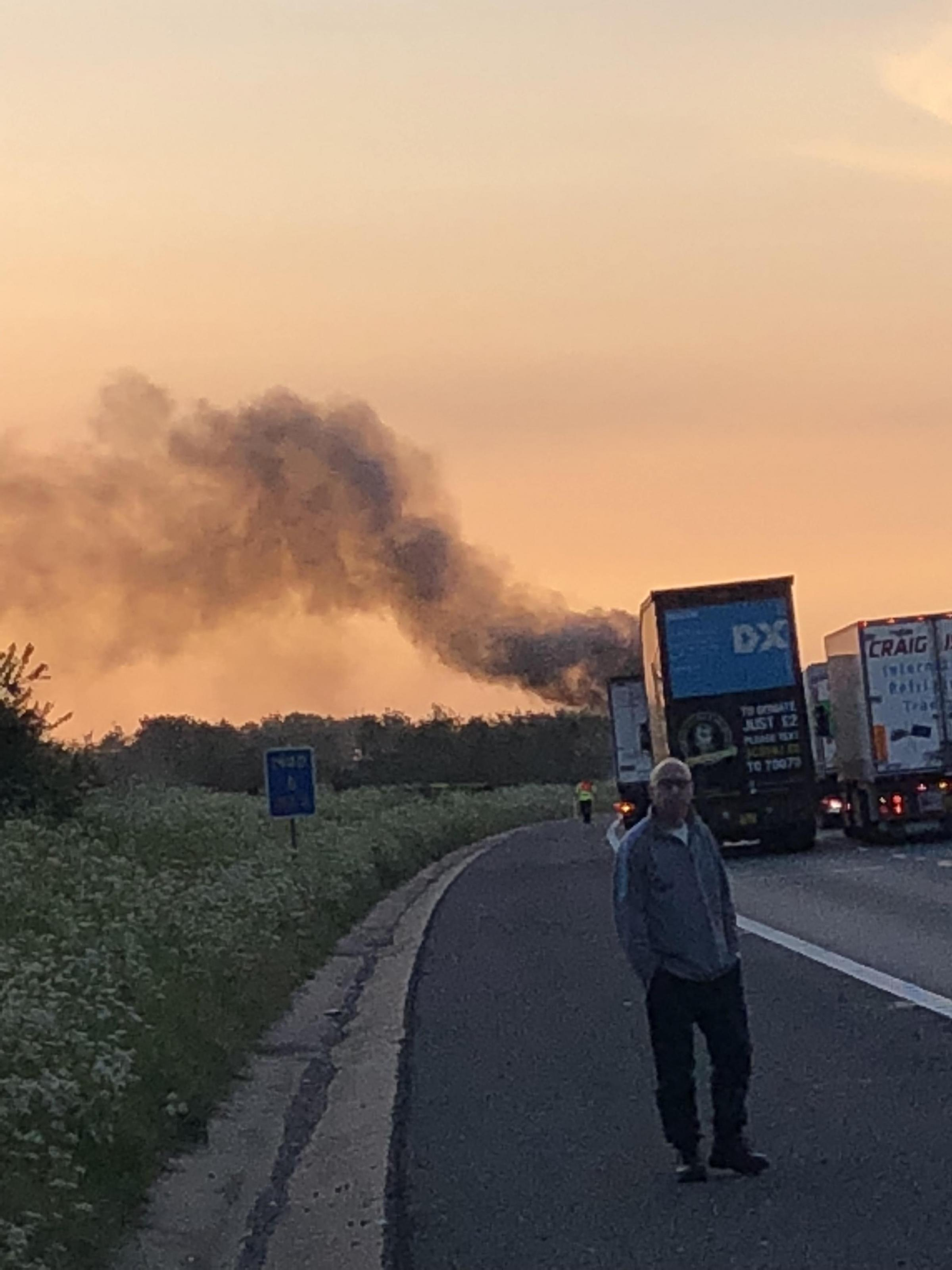 Kudrat Ali at the side of the road with the HGV fire in the background