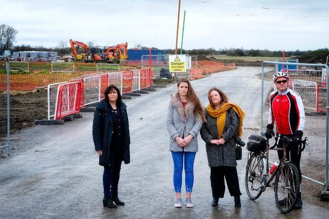 County councillor Jenny Hannaby, accident victim Elliann Edwards, councillor Jane Hanna and John Tranter, chair of Cycling UK Wantage at one of the entrances to the massive building site at Grove. They claim that mud from the site is causing an increase i