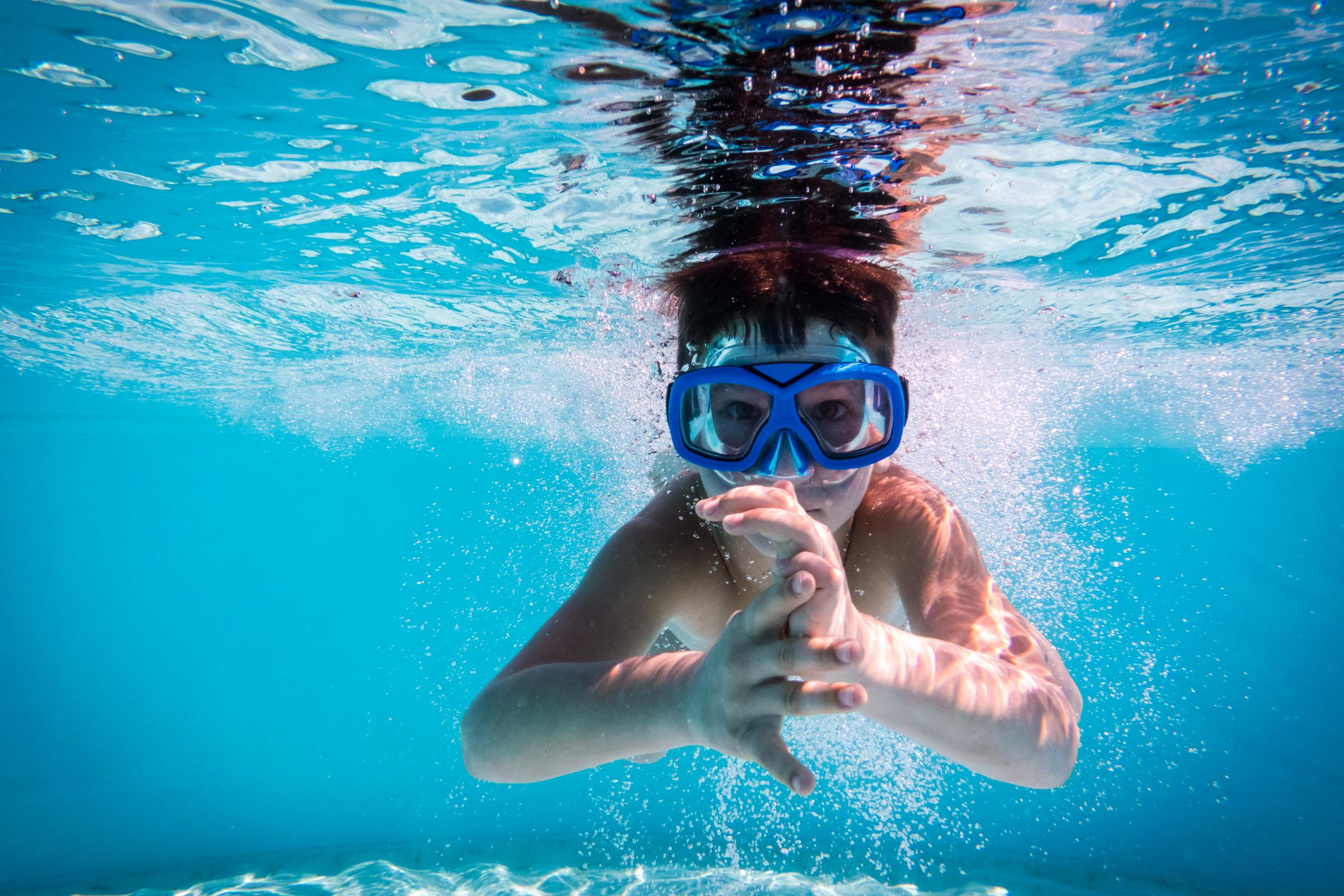 Boy in mask dive in swimming pool. Getty Images