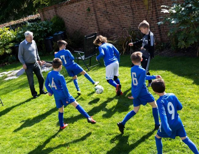 St Edmunds U8's play football with Bridge House resident Colin Bladon