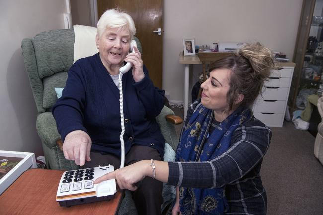 Rachael Dredge of Soha Housing's Independent Living service demonstrating the Housing Proactive phone welfare service to a resident. Pic Frank Dumbleton