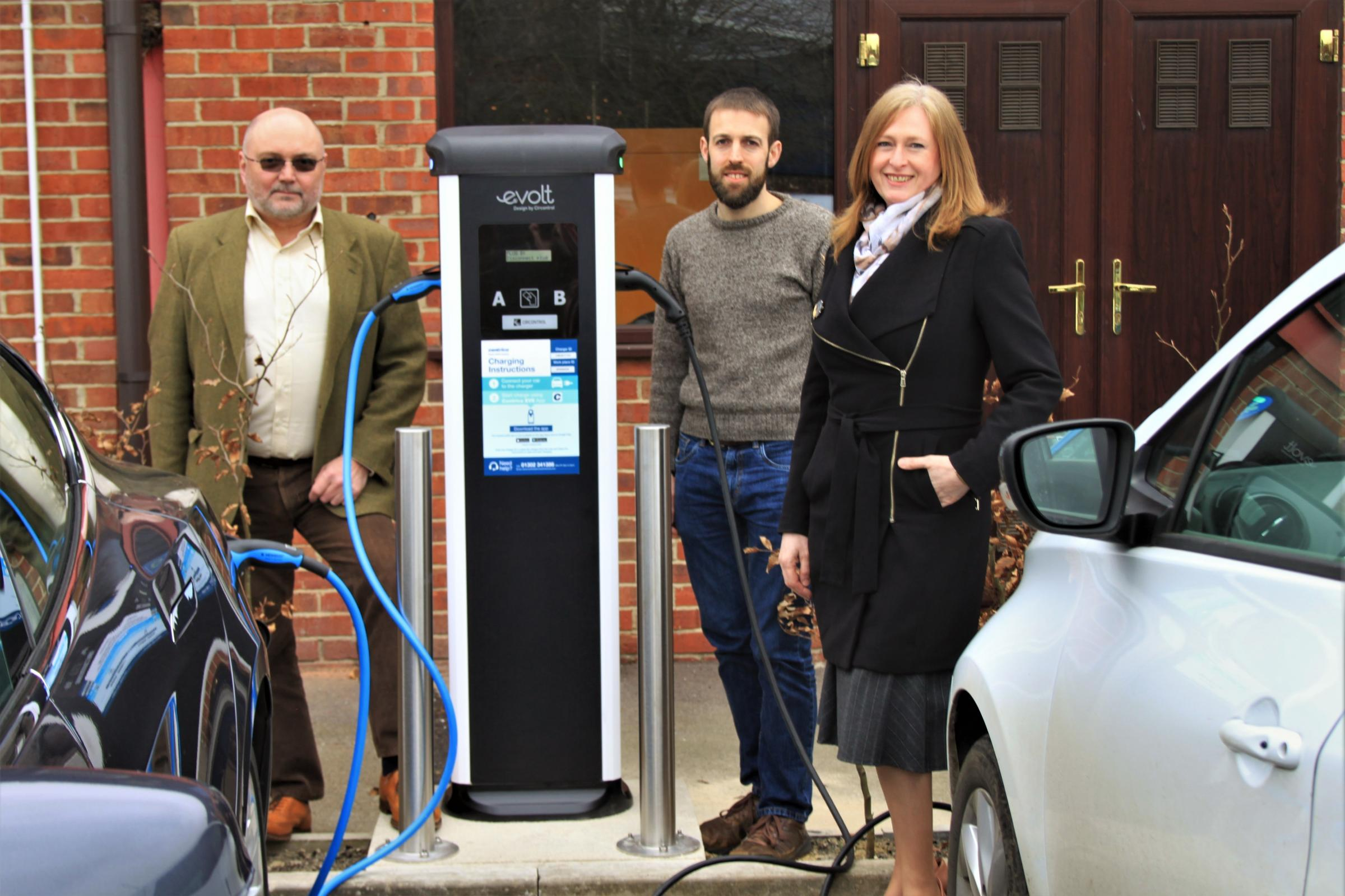 Electric vehicle owners Martin Loveridge and David Gruar with Jennings' Rhonda Leighton at the new electric vehicle charging station at Monument Business Park in Chalgrove Pic Monument Business Park
