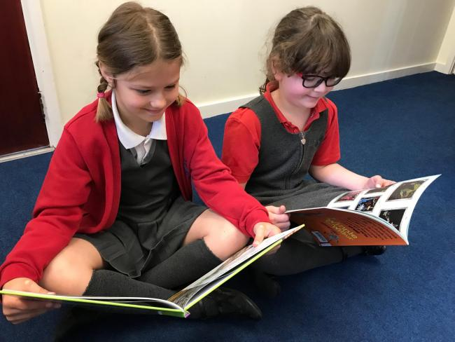 Pupils Hannah Sear (L) and Phoebe Miles (R) at a school near Wantage will be able to enjoy more books after a donation. Picture: Grove Primary